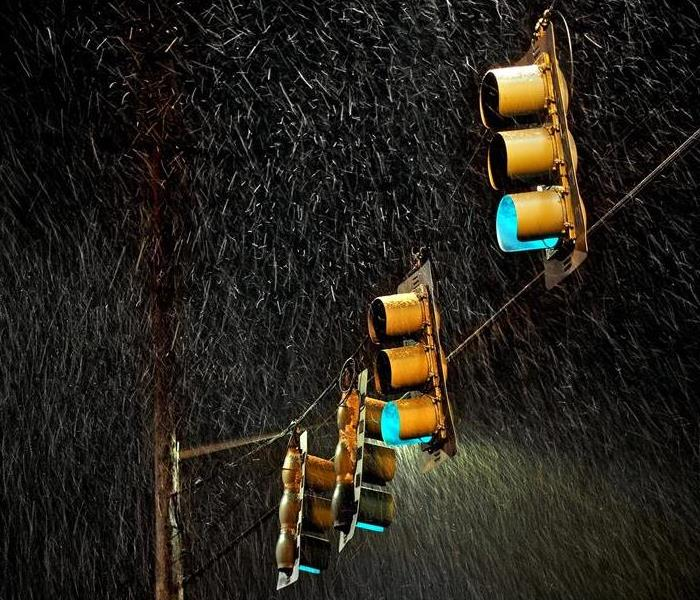 Four traffic lights and power lines on a dark night in a rain storm.